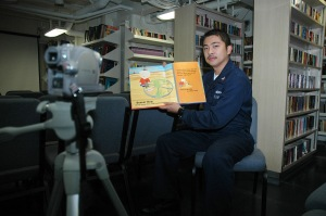 051128-9866B-606 San Diego (Nov. 28, 2005) - ShipÕs Serviceman 2nd Class Billy Amurao reads a childrenÕs book into a video camera in the library of the amphibious assault ship USS Peleliu (LHA 5) as part of a preparation for the United Through Reading program for when the ship deploys this spring. Amurao has a five-year-old son. U.S. Navy photo by Journalist 2nd Class Zack Baddorf (RELEASED)